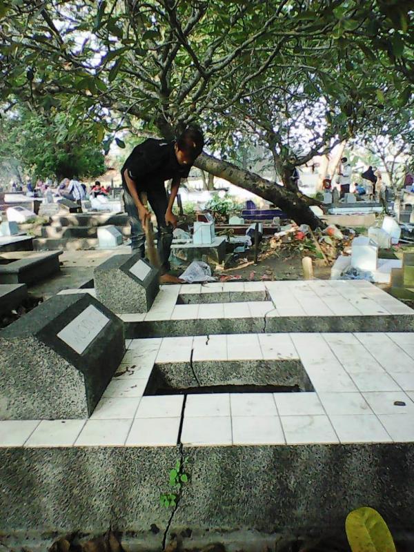 Seorang anak tengah membersihkan makam. Mereka memanfaatkan momentum ramainya warga berziarah meraih rezeki sebagai tukang sapu makam. (Taryani)